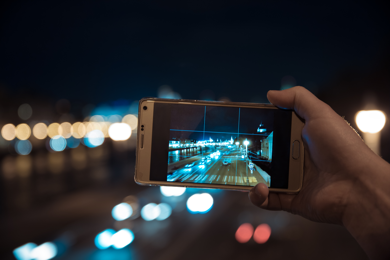 smartphone capturing city lights at night