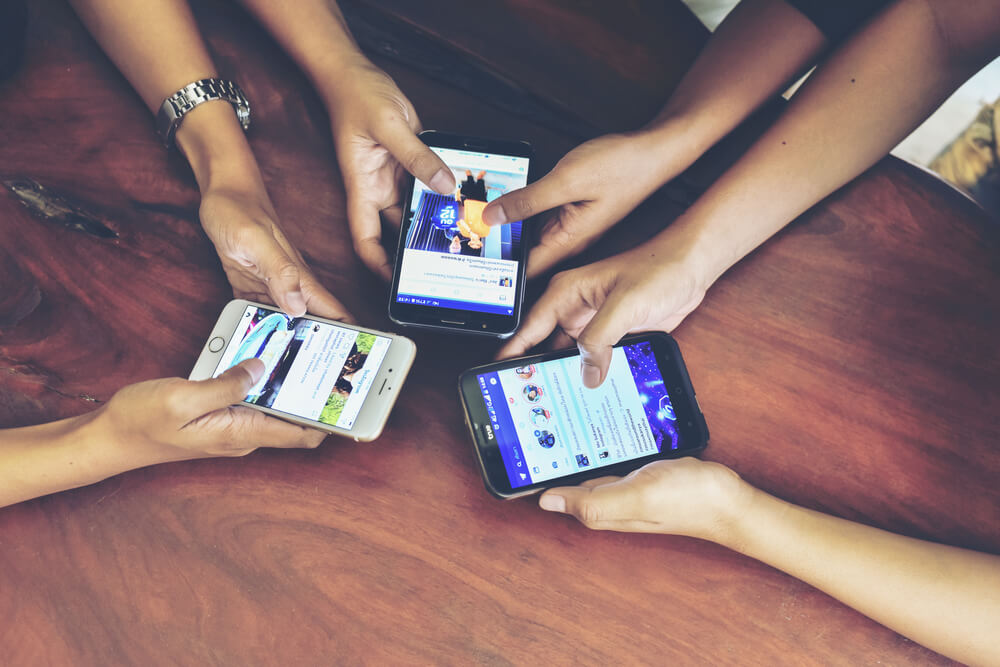 three pair of hands holding smartphones with their social media pages open.