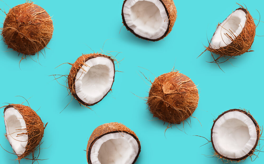 several coconut husks and meat on plain blue green background.