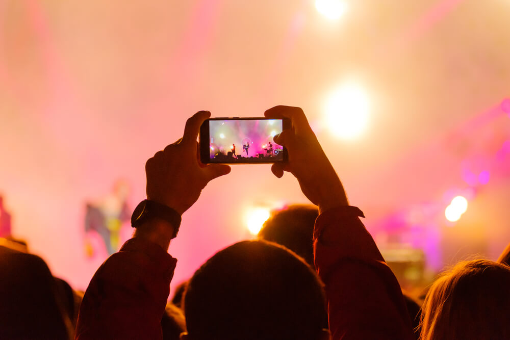 guy taking photo of a concert stage using his smartphone. - flash on iPhone camera