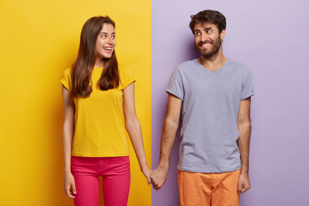 Caucasian couple wearing yellow and purple shirt.