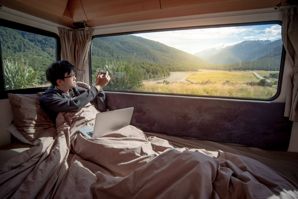 Digital nomad on his bed, taking a photo of the view outside his window.