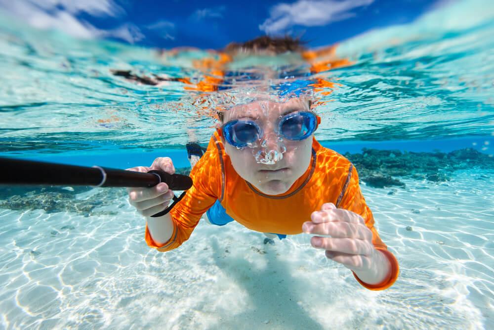 kid taking a selfie underwater.