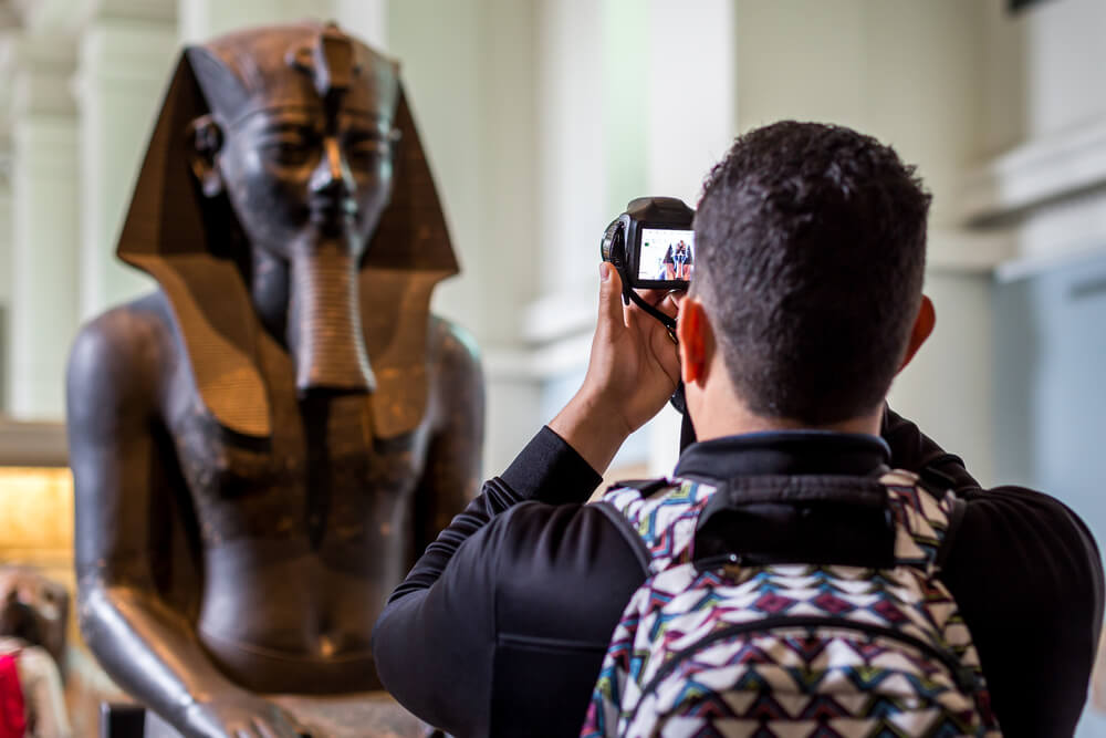 photographer taking a photo of an Egyptian statue.
