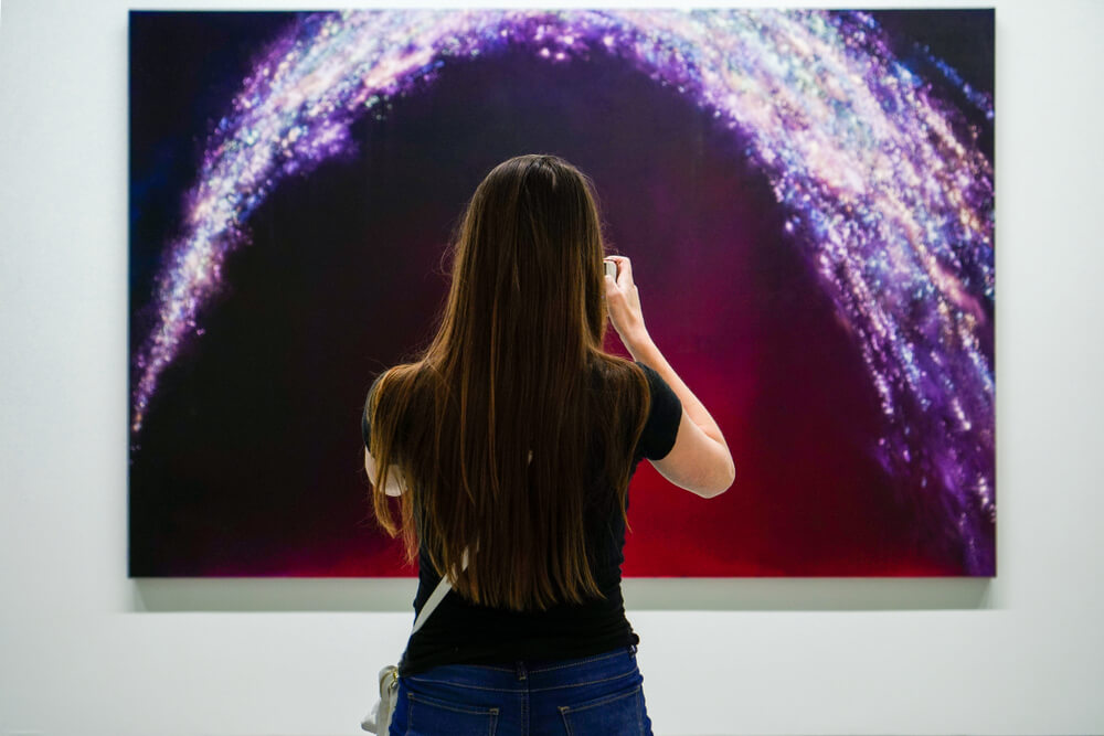 girl capturing a photo of painting of bright lights in dark magenta background.