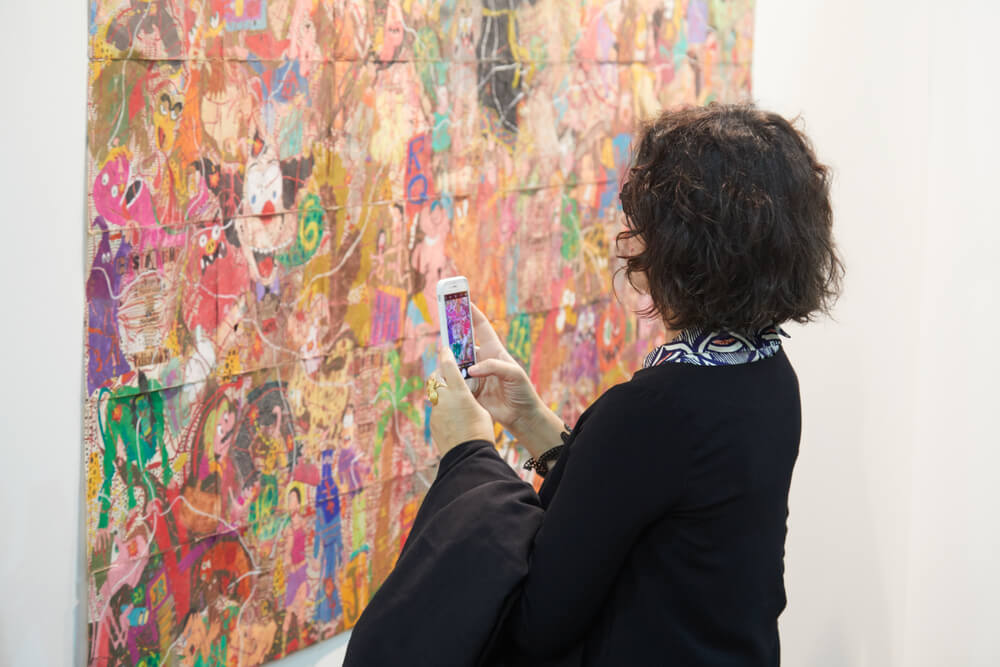 girl taking photo of an artwork with her iPhone - photograph artwork with iPhone