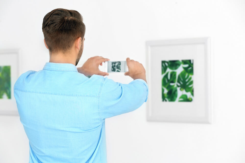 guy taking a picture of a framed painting - photograph artwork with iPhone