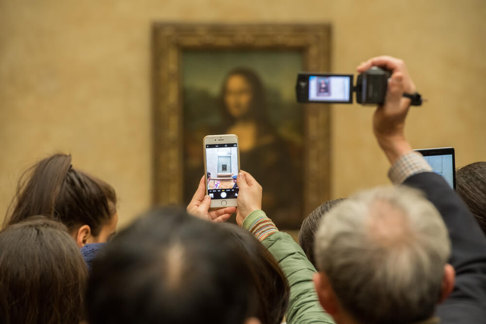 The Mona Lisa being photographed by onlookers.