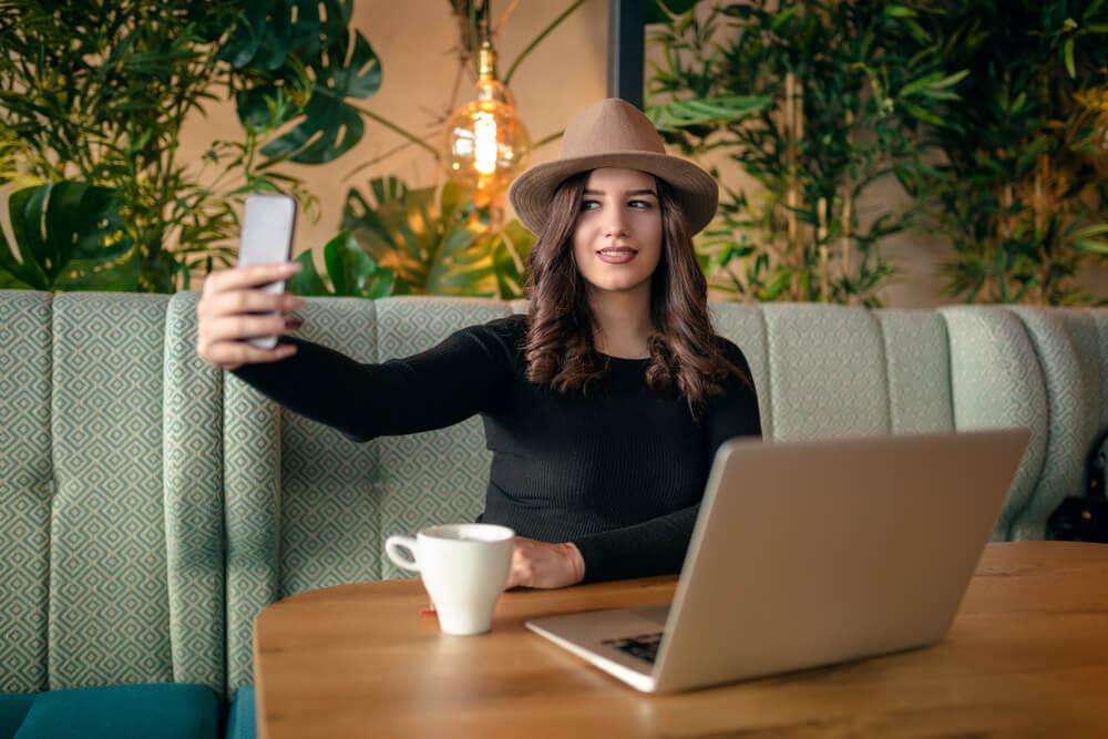 hipster girl taking a selfie on a cafe on her iPhone.
