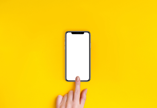 Top view of a woman hand using phone on yellow background.