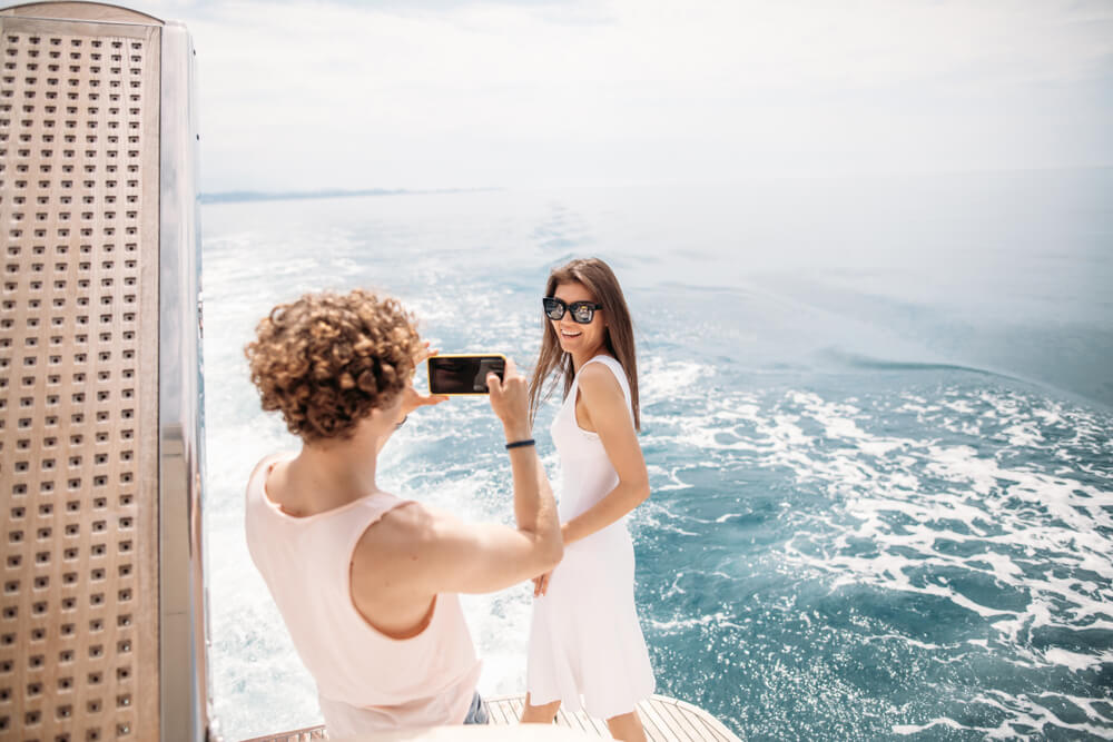 curly-haired woman taking a photo of a long-haired woman on a boat.