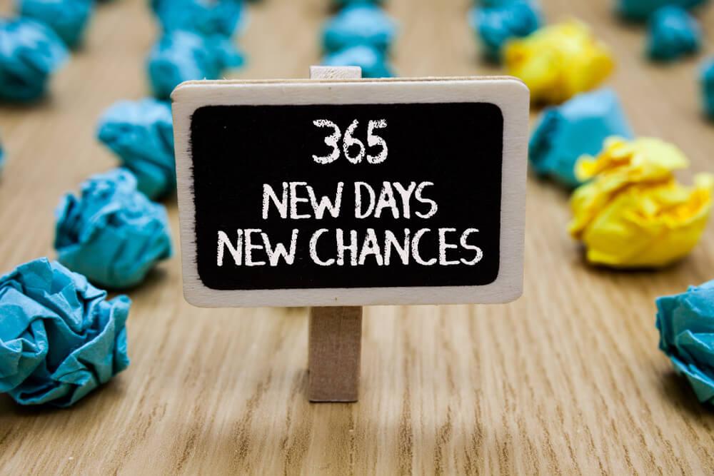 "small, artsy cardboard saying ""365 new days, new chances"""