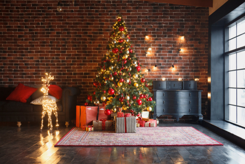 New Year interior with red brick wall background, decorated fir tree with garlands and balls, dark drawer and deer figure