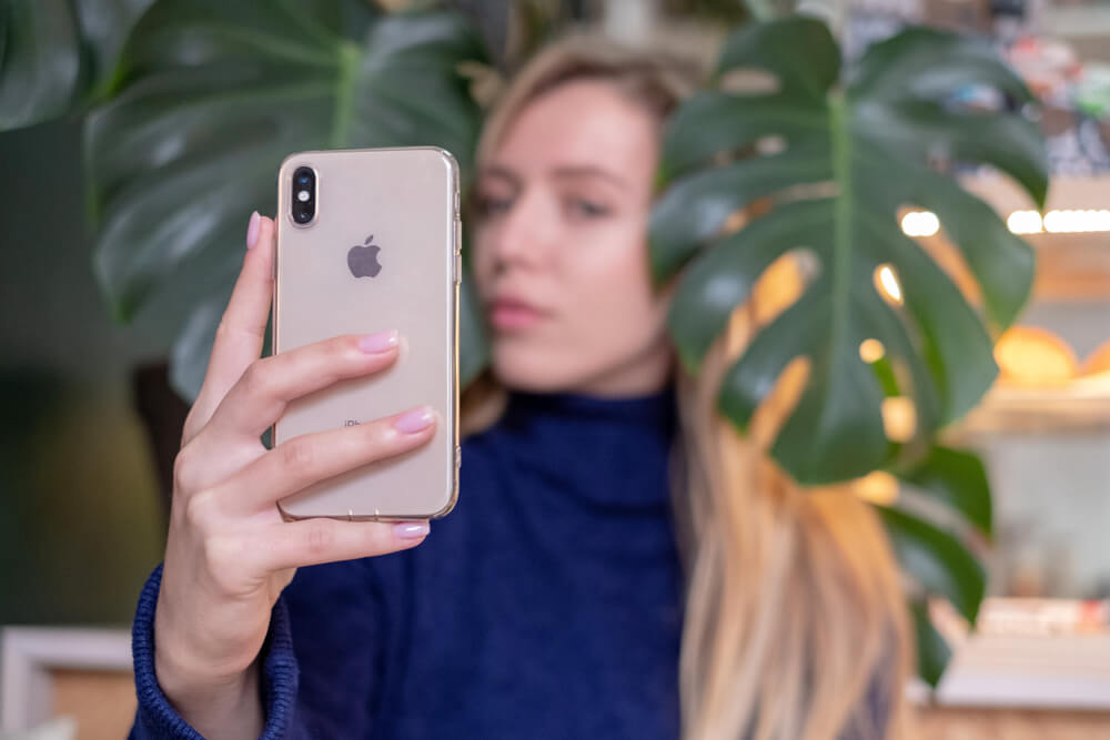 blonde girl taking a selfie with plant.