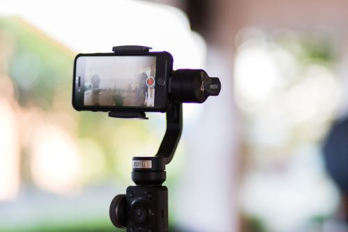 Mobile phone iphone 8 is shooting a video using gimbal zhiyun smooth 4 background is bokeh in the morning Video filming concept