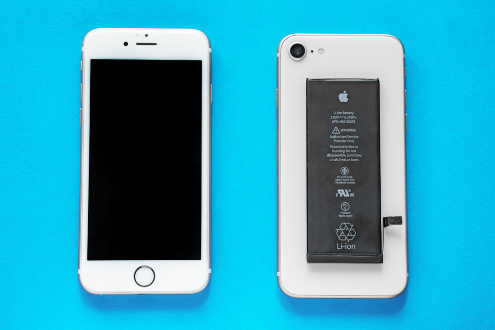 two white iPhones, with one of them having its battery taken out.