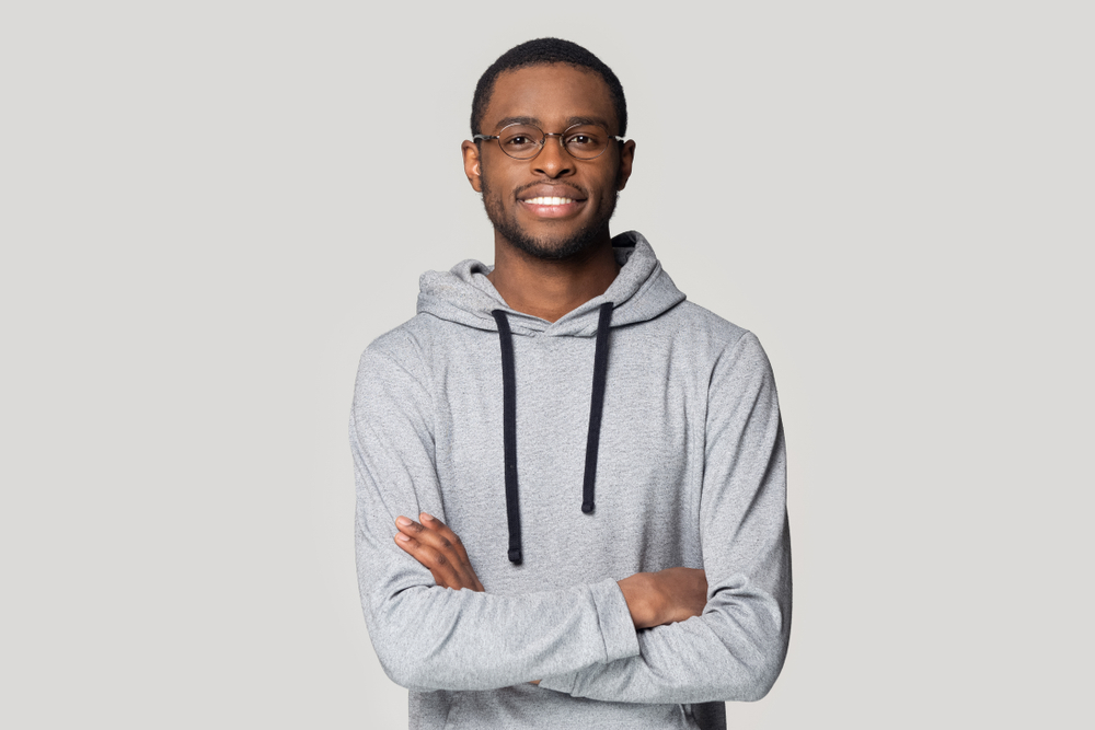 smiling african-american skinhead guy wearing eyeglasses and hoodie.