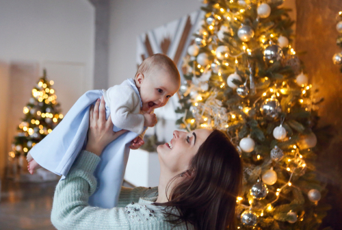 Beautiful happy mother with lher ittle daughter in knit sweater sitting on the background of Christmas interior hugging together and smiling
