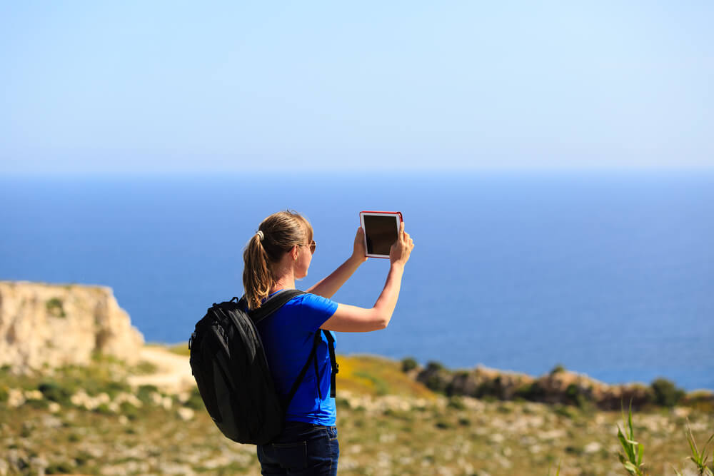Girl in ponytail taking photo of blue sky using iPad. - zoom or crop an iPhone photo