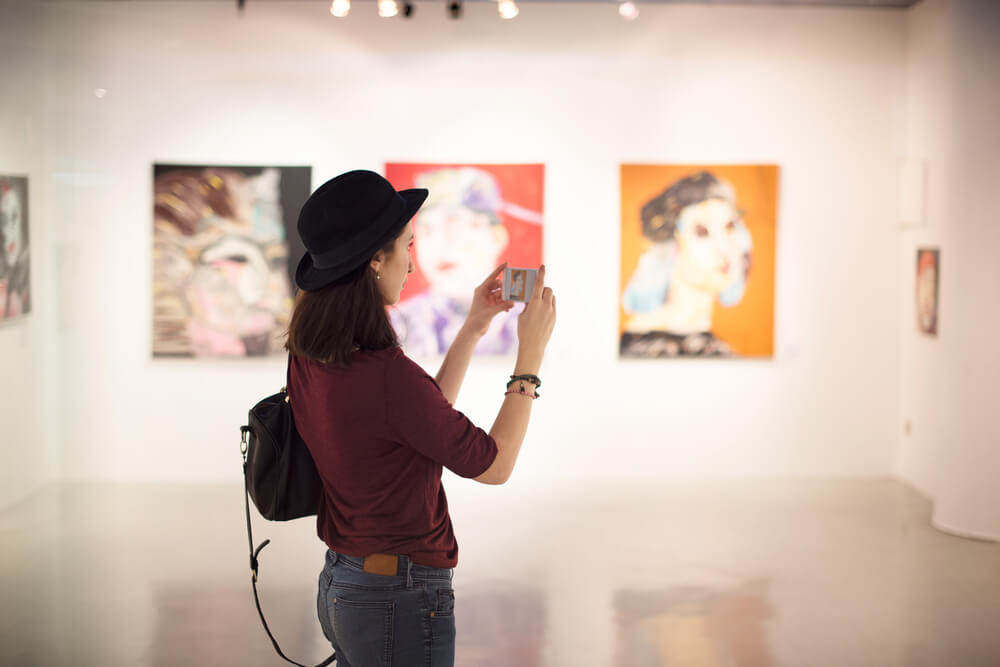 young woman taking pictures of paintings in a gallery.