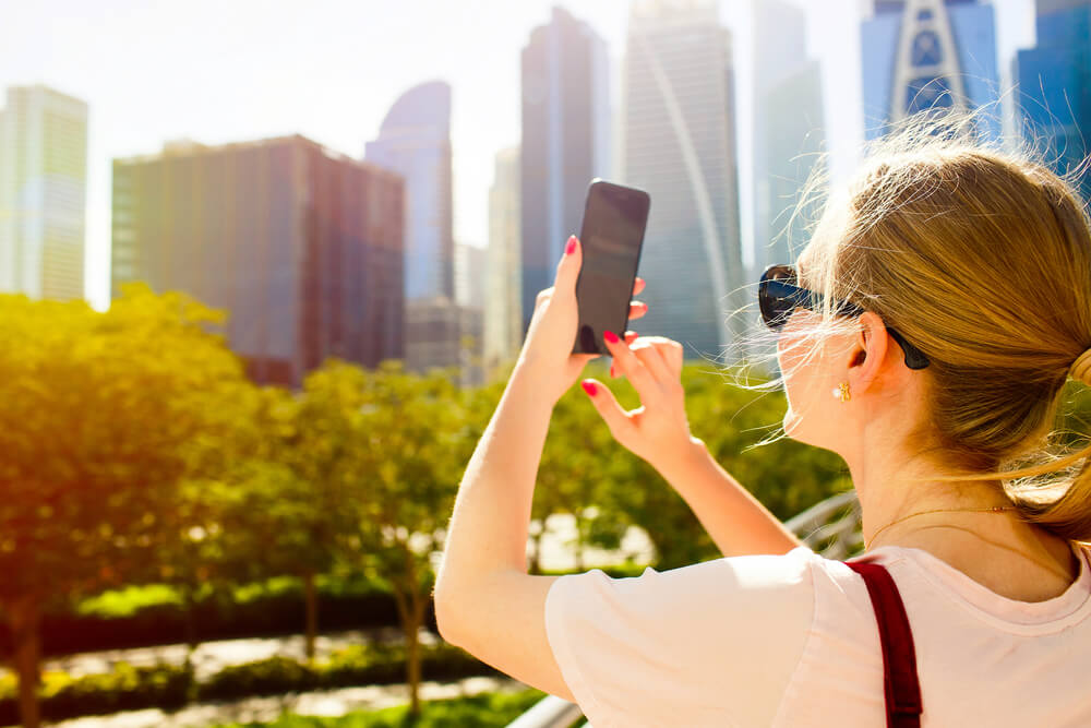 blonde girl taking photos of the bright sun in an urban area. - sun damage an iPhone