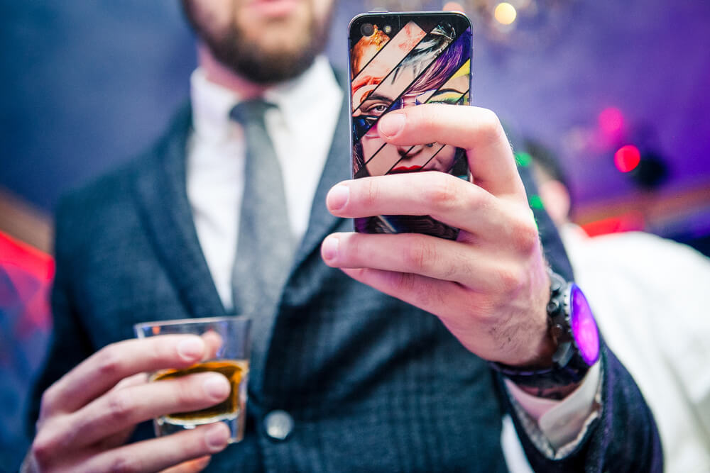 Man in a suit holding a shot of whiskey on the other hand and iPhone on one hand.