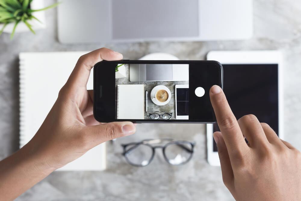 iPhone taking photo of flat-lay of iPad, eyeglasses, laptop, and notebooks.