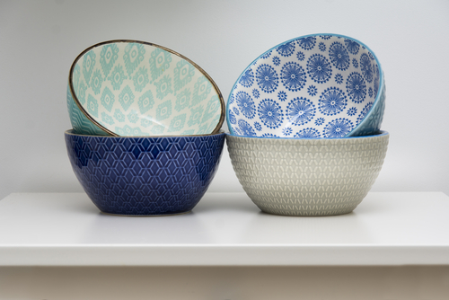 Four designer ceramic bowls in different colors stacked together.