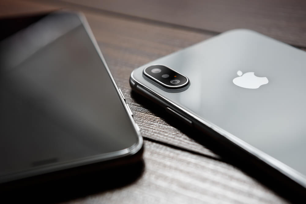 Two iPhones on wooden table.