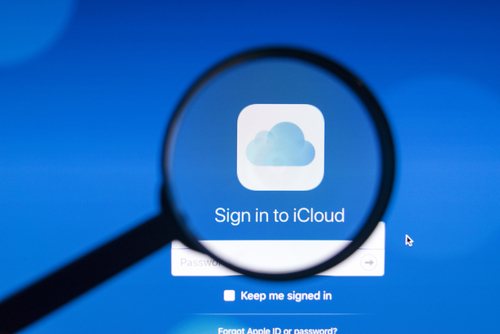 Photo of icloud homepage on a iMac monitor screen through a magnifying glass