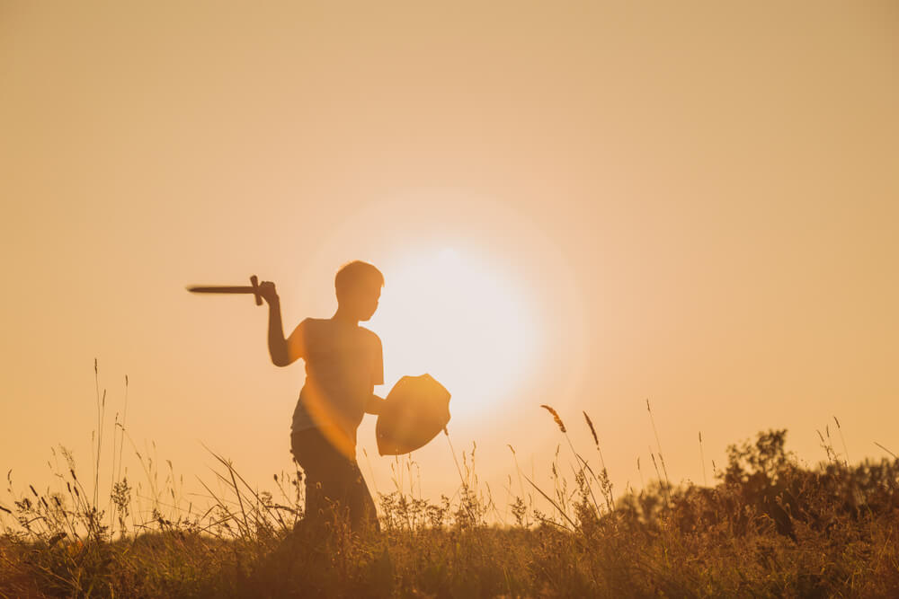 silhouette of a kid holding a sword and a shield.
