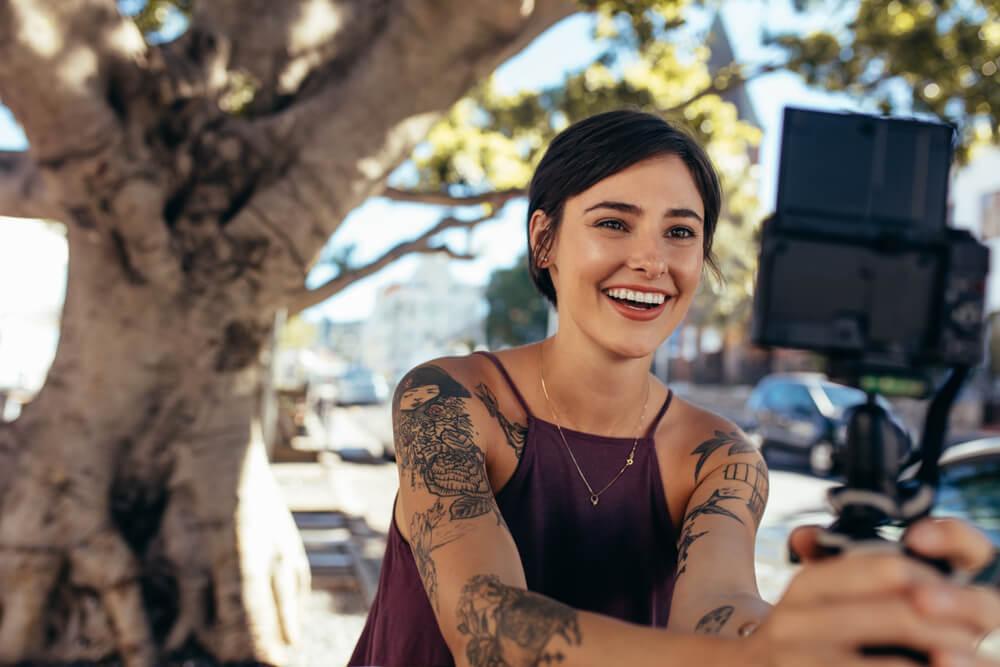 tattooed content creator filming herself.