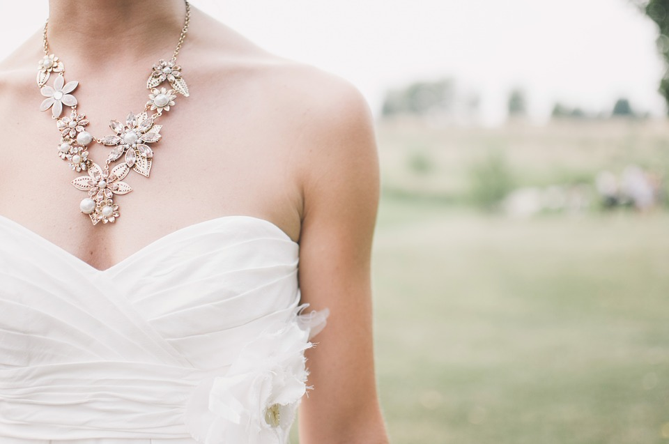 A girl on a a white dress wearing a necklace