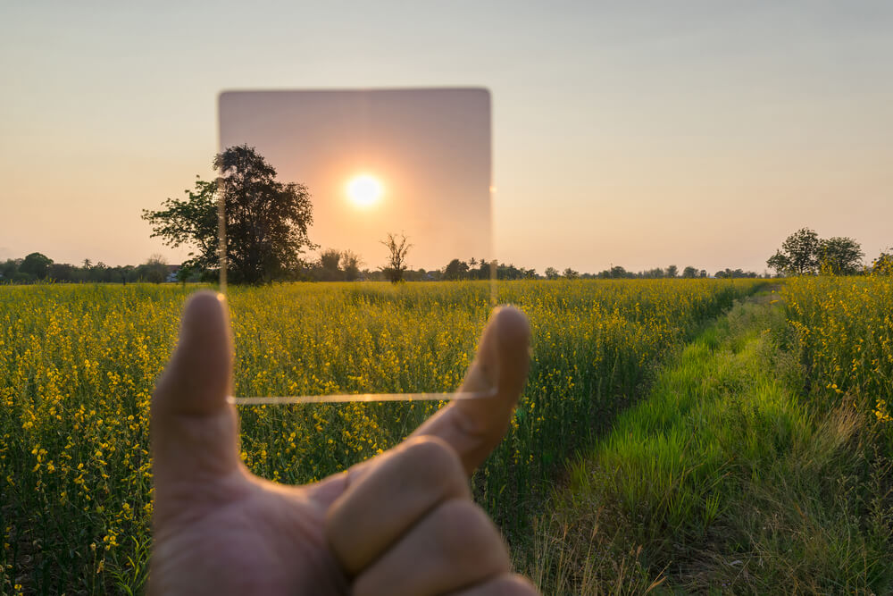 Holding up a Neutral Density Filter against grassland and bright sun.
