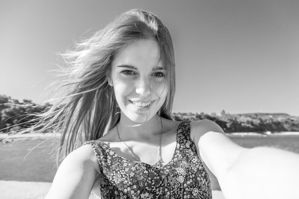 blonde girl taking a selfie in black and white filter.