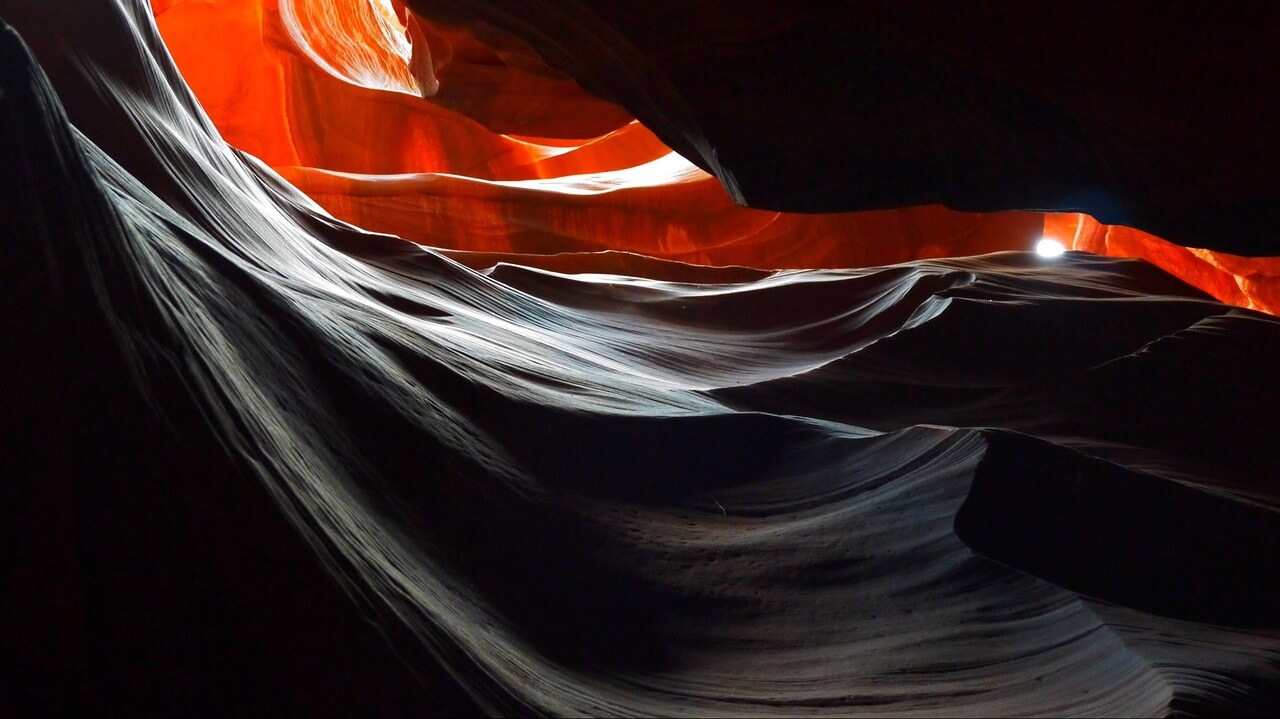 extremely dark part of the Antelope Canyon with a little fiery red light.