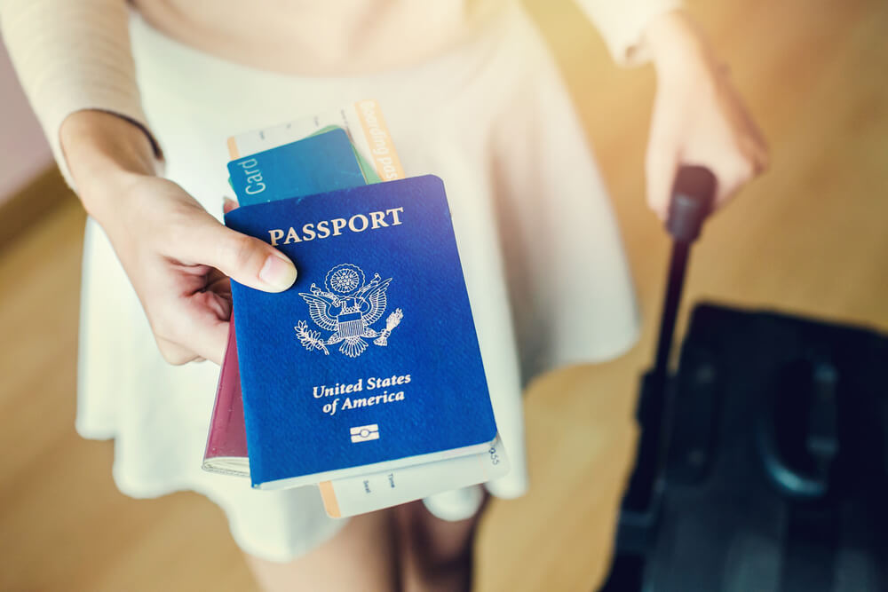 a girl holding her US passport and luggage. - passport photo iPhone