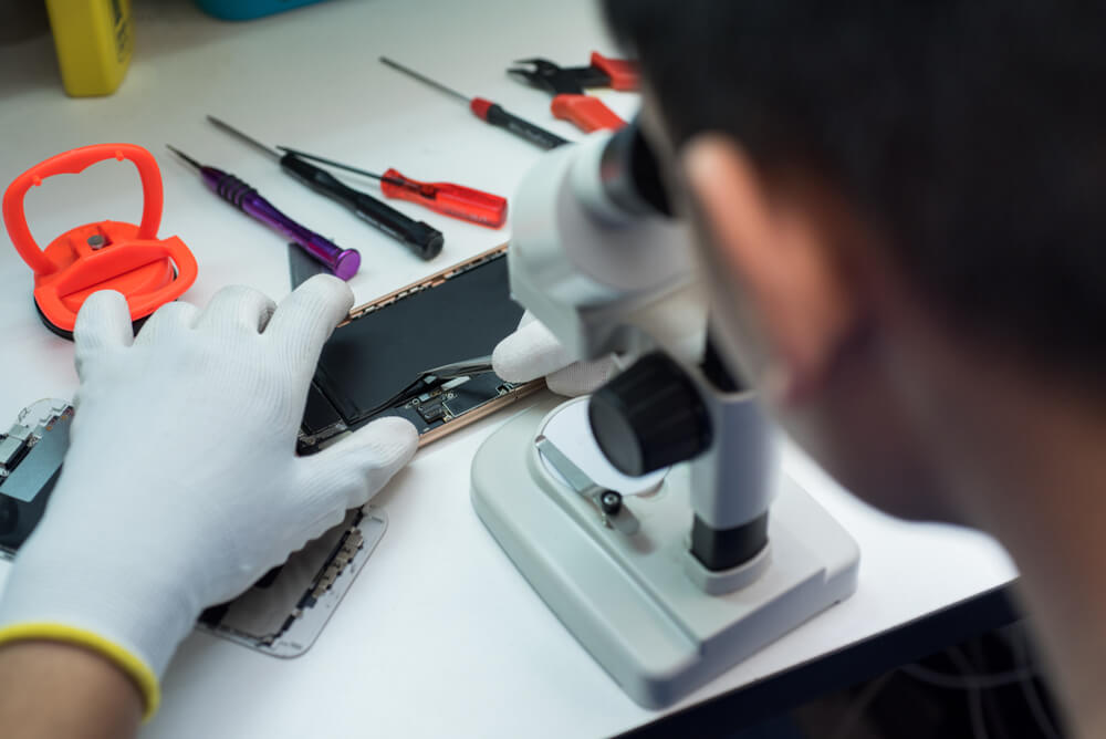 a technician checking the internal parts of an iPhone. - replace iPhone camera