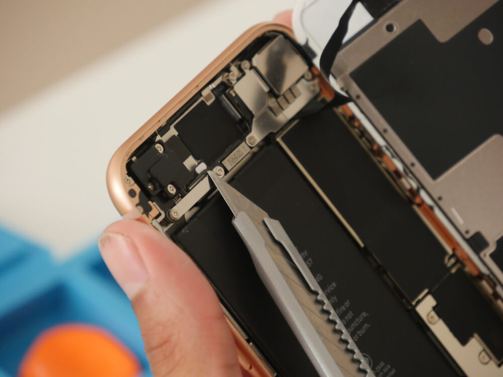 prying open the rear screen of a rose gold iPhone. - replace iPhone camera