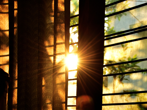Golden sunrise behind a curtained window.