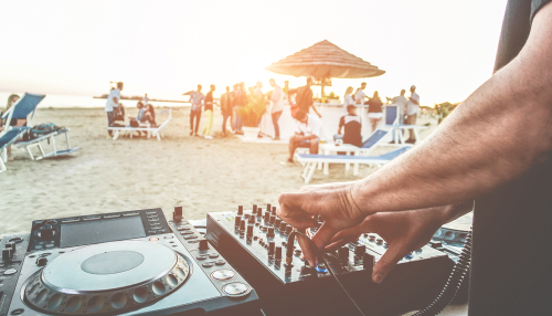 Dj mixing at sunset beach party in summer vacation outdoor - Disc jockey hands playing music for tourist people in chiringuito kiosk bar - Event, music and fun concept
