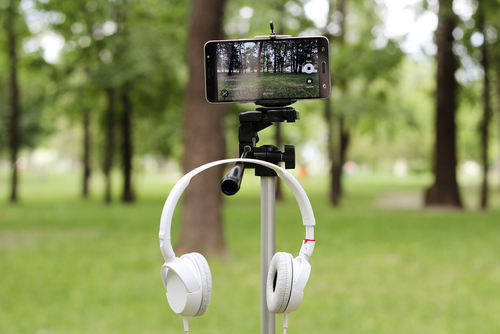 White earphones and modern smartphone fixed on fluid tripod are ready to record video in the park, education and technology, summer outdoor