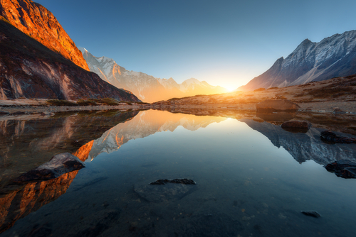 Beautiful landscape with high rocks with illuminated peaks, stones in mountain lake, reflection, blue sky and yellow sunlight in sunrise. Nepal. Amazing scene with Himalayan mountains. Himalayas.