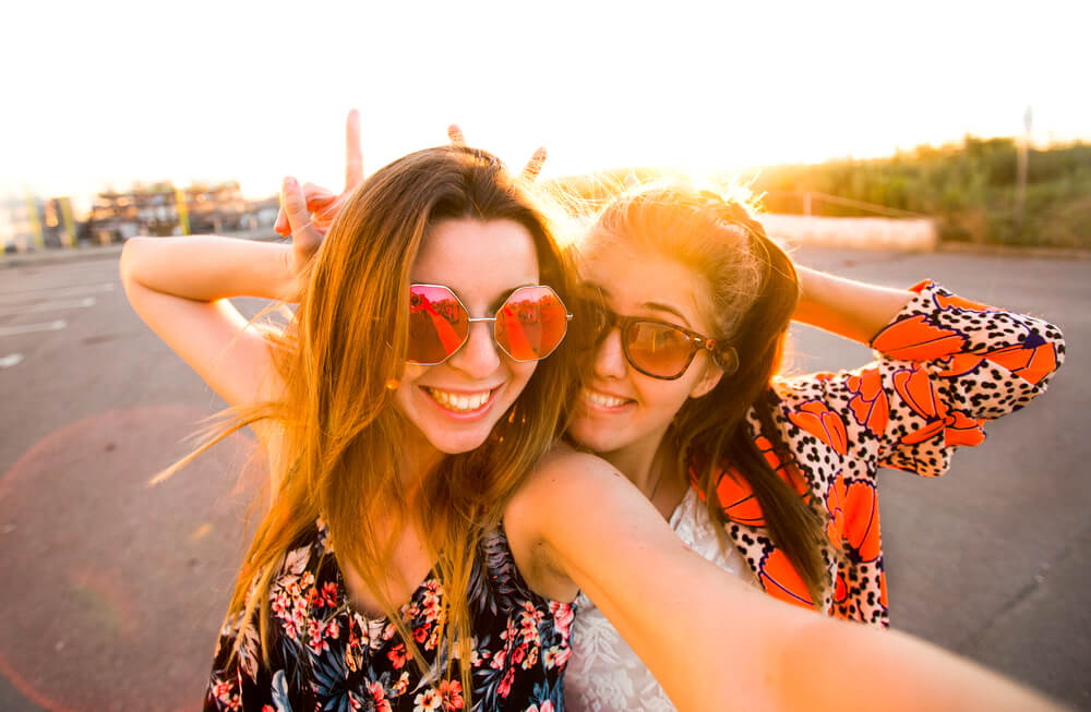 Two girls taking a fun selfie behind the sunset.