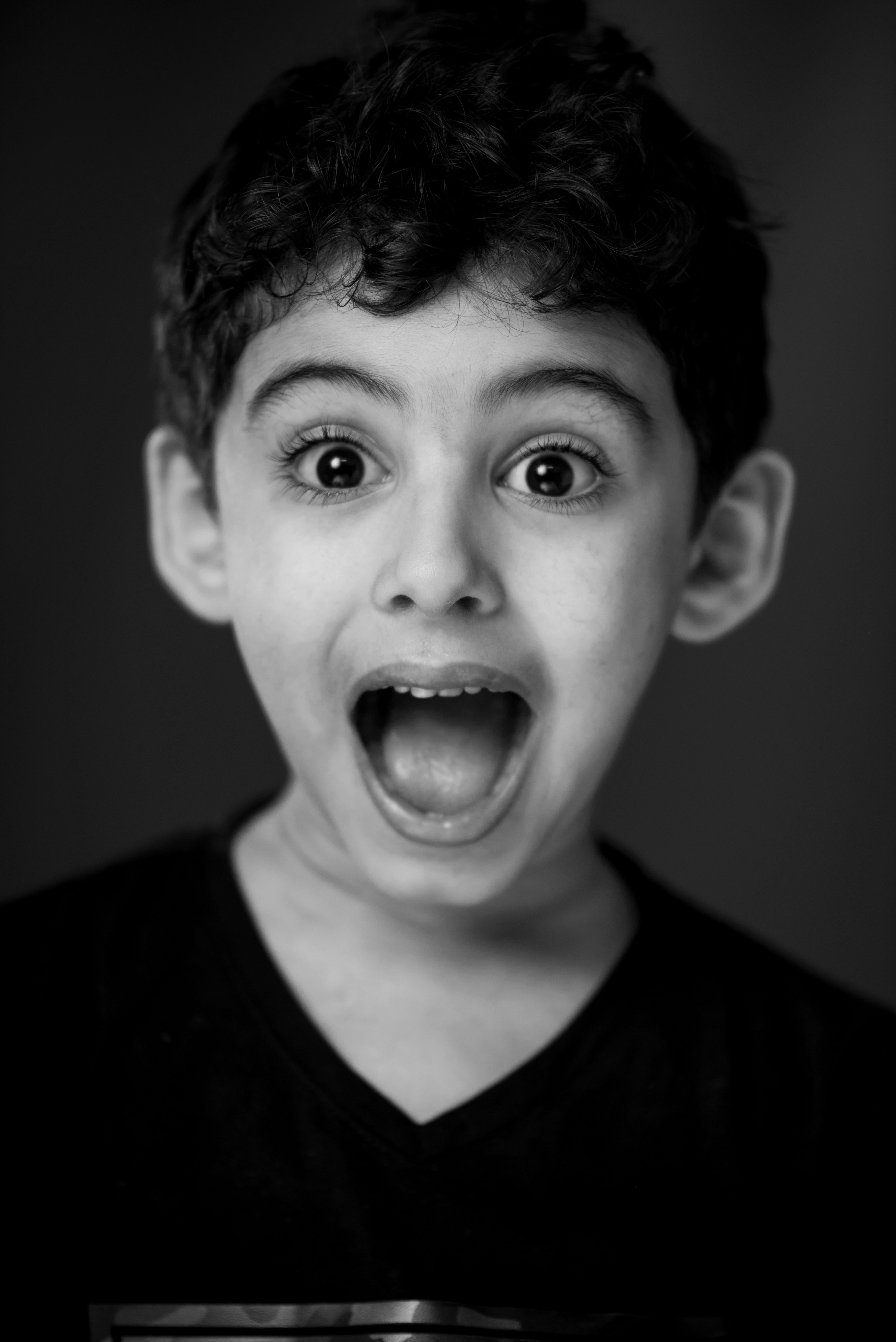 cute kid with smiling, gaping mouth in black and white filter.
