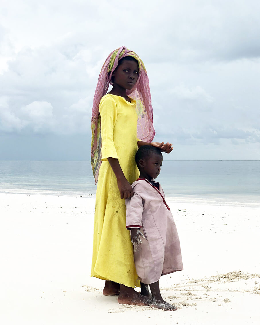 a young girl from Tanzania with her little brother standing at the white-sand beach. - make money iPhone photos