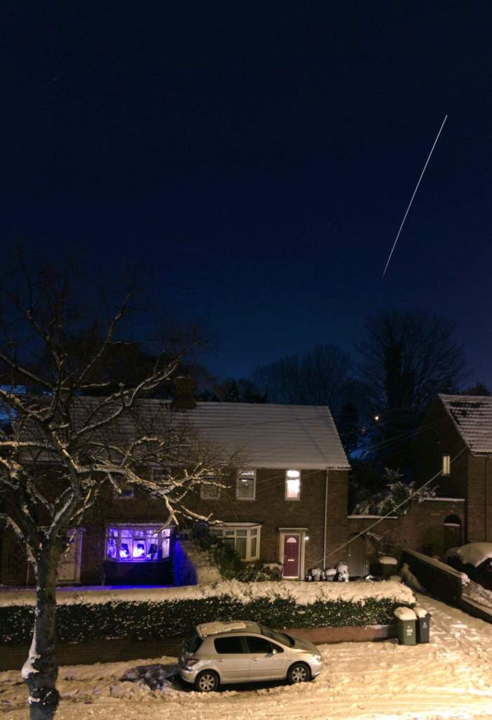 a photo of the ISS at night and a snowy house and car.