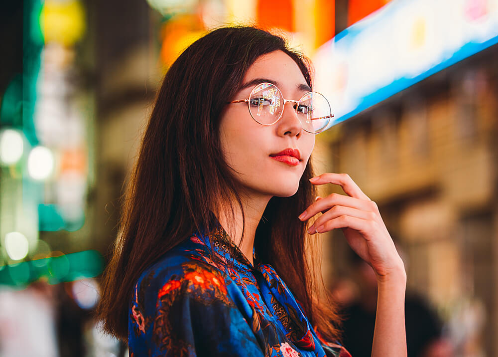 Asian girl with glasses with a colorful bokeh background.  - depth in iPhone