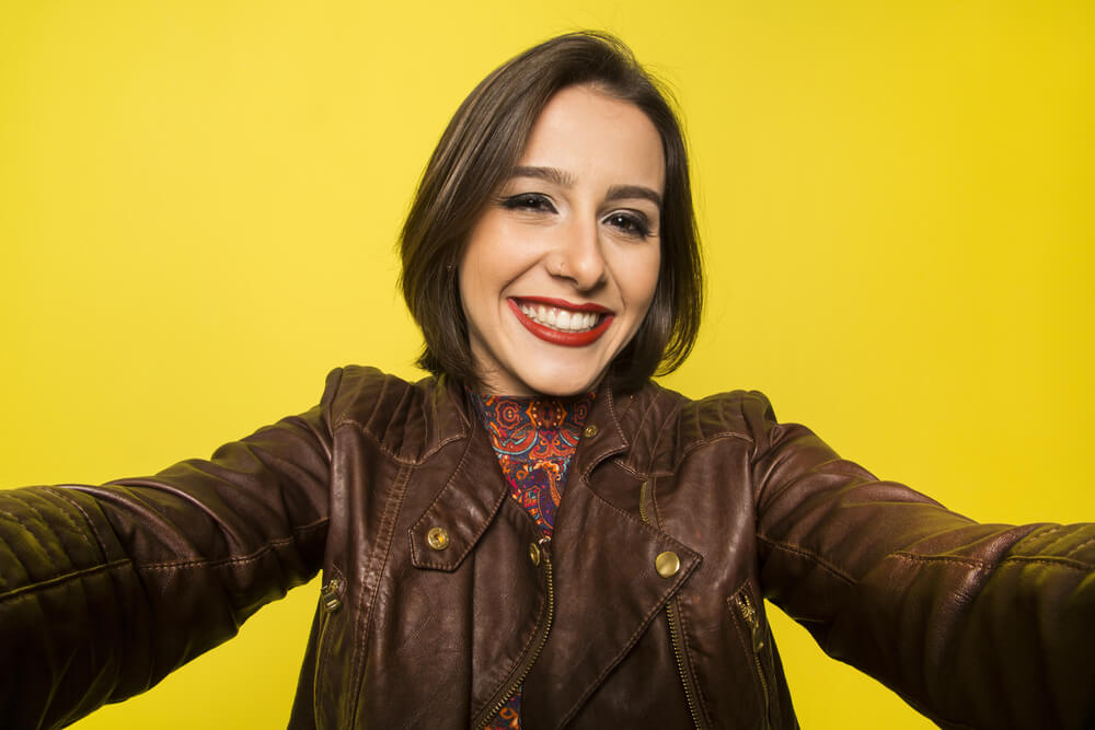 Cute woman in brown leather jacket takes a selfie in plain yellow background. - selfie lights iPhone