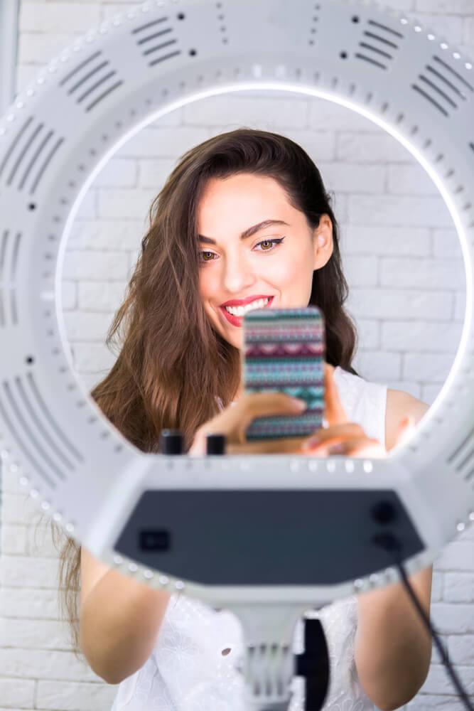 girl taking a selfie in front of a selfie light - selfie lights iPhone